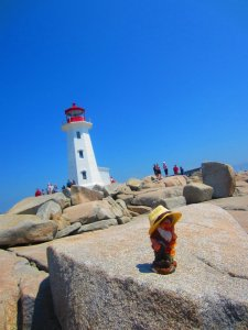 Frederick the gnome poses with the lighthouse at Peggy's Cove in Nova Scotia, Canada