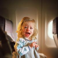 A not so peaceful little girl crying in her airplane seat