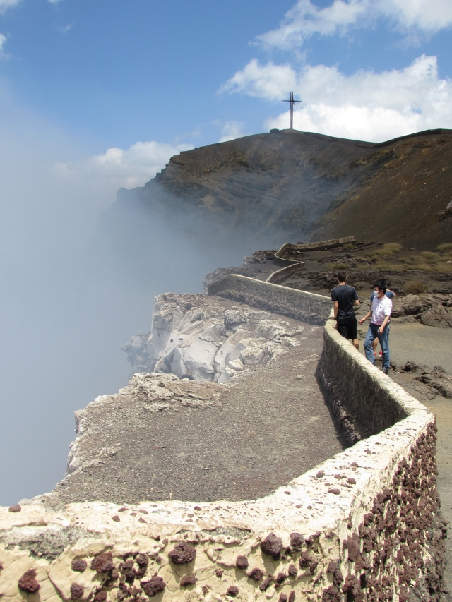 Tourists look down into the smokey Mouth of Hell where women and children were sacrificed