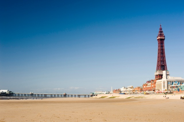 Open expanse of sand at the Blackpool beach with the Blackpool Tower and waterfront on the right and central pier in the distance